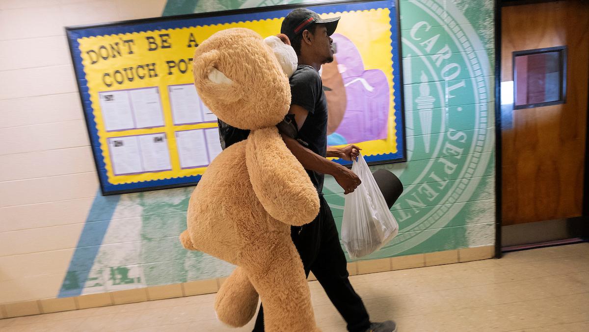 A man carries a large stuffed bear.