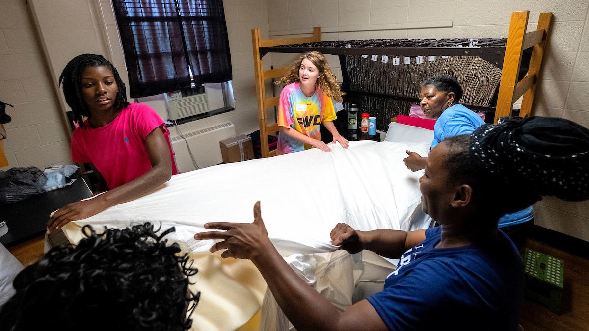 People make a bed inside a dorm room.