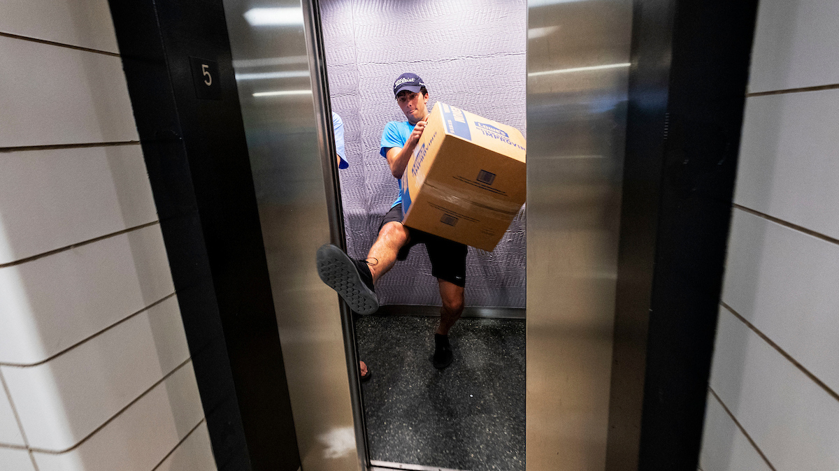 A student carries a large box on an elevator.