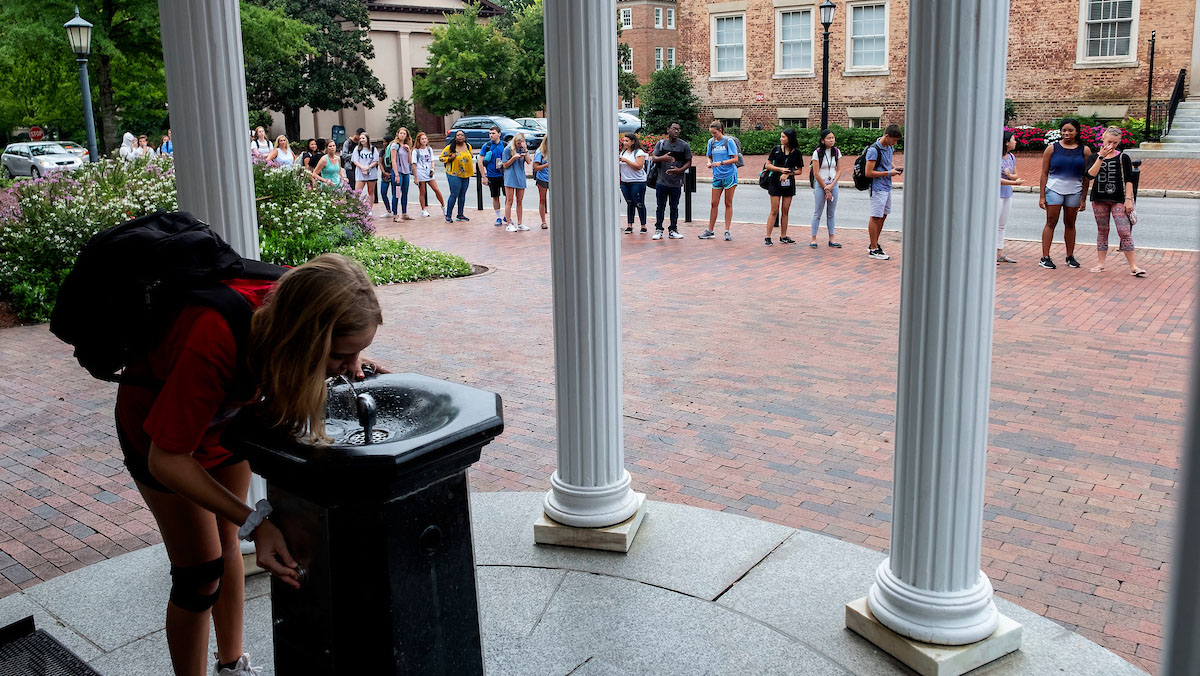 A student drinks from the Old Well.