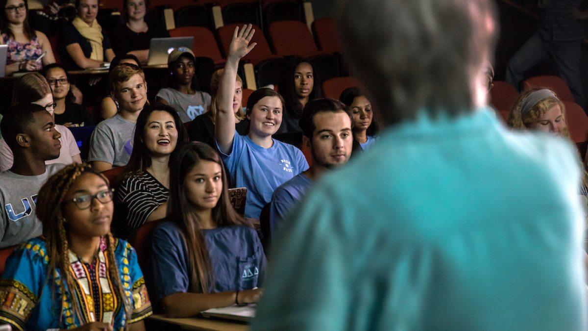 A student raises her hand in class.