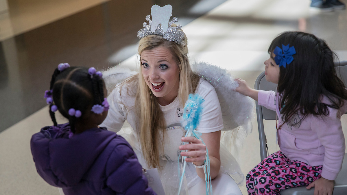 A student dressed up like a toothfairy talks with young children.