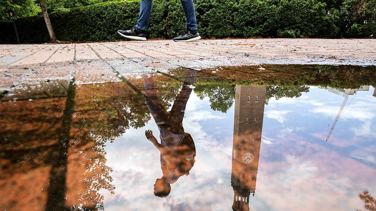 The reflection of a student in a puddle.
