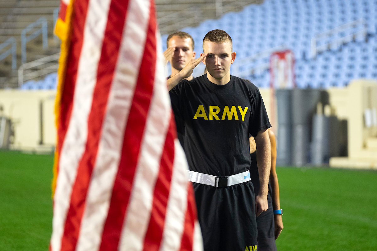 A ROTC cadet salutes the American flag.