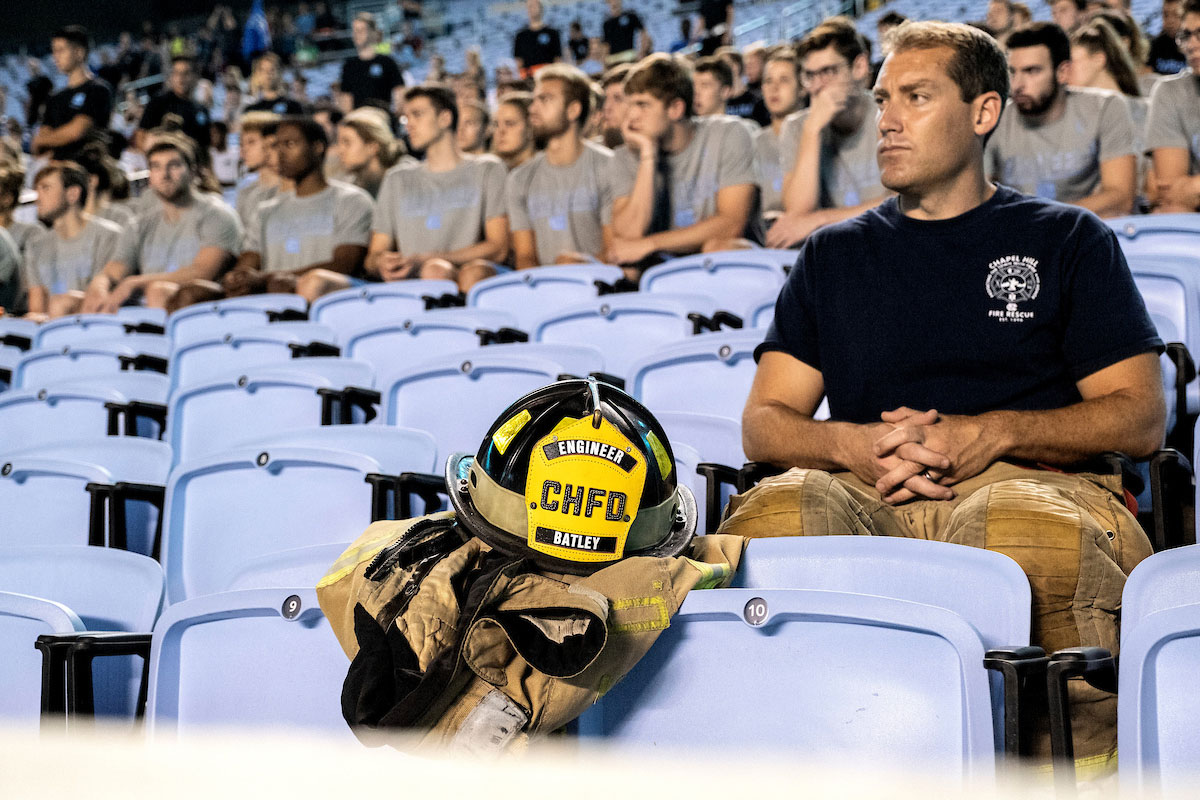 A firefighter sits at Kenan Stadium with his equipment.