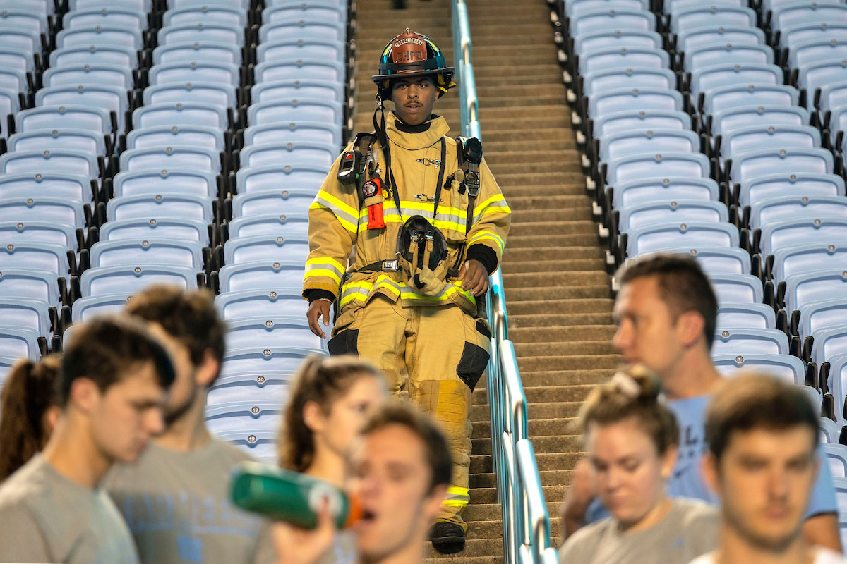 A firefighter in turnout gear walks up the steps at Kenan Stadium.