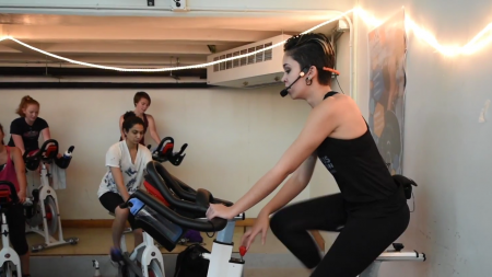 Andrea Orengo rides a stationary bike while leading a class.