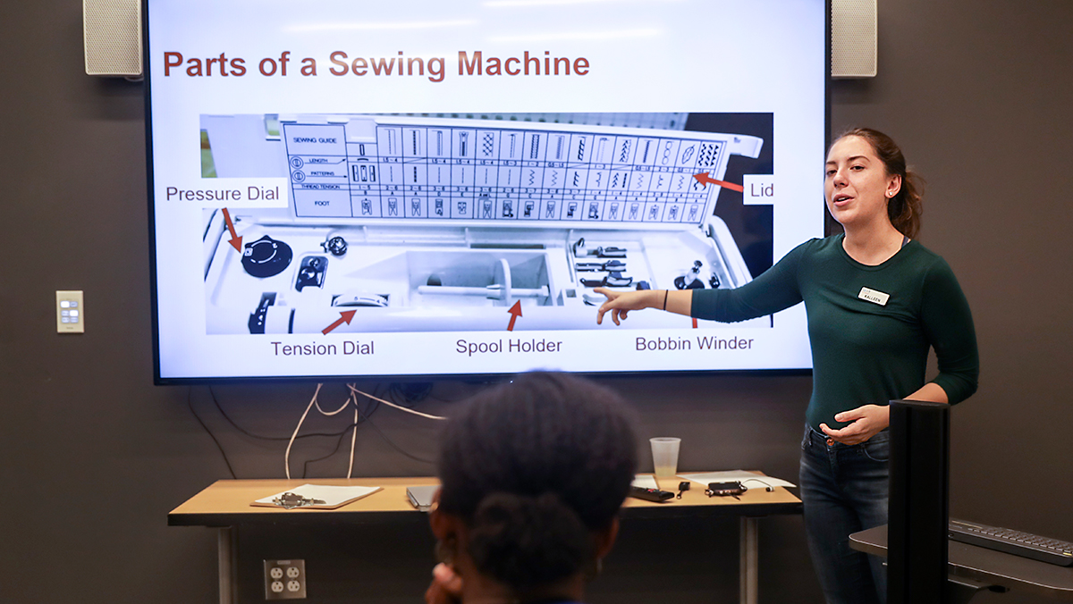 A student shows the parts of a sewing machine.