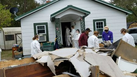 Students remove drywall from a house damaged by flooding.