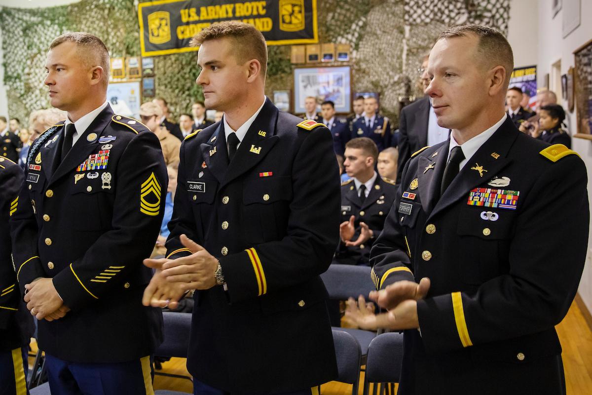 Three men in military uniform clap.