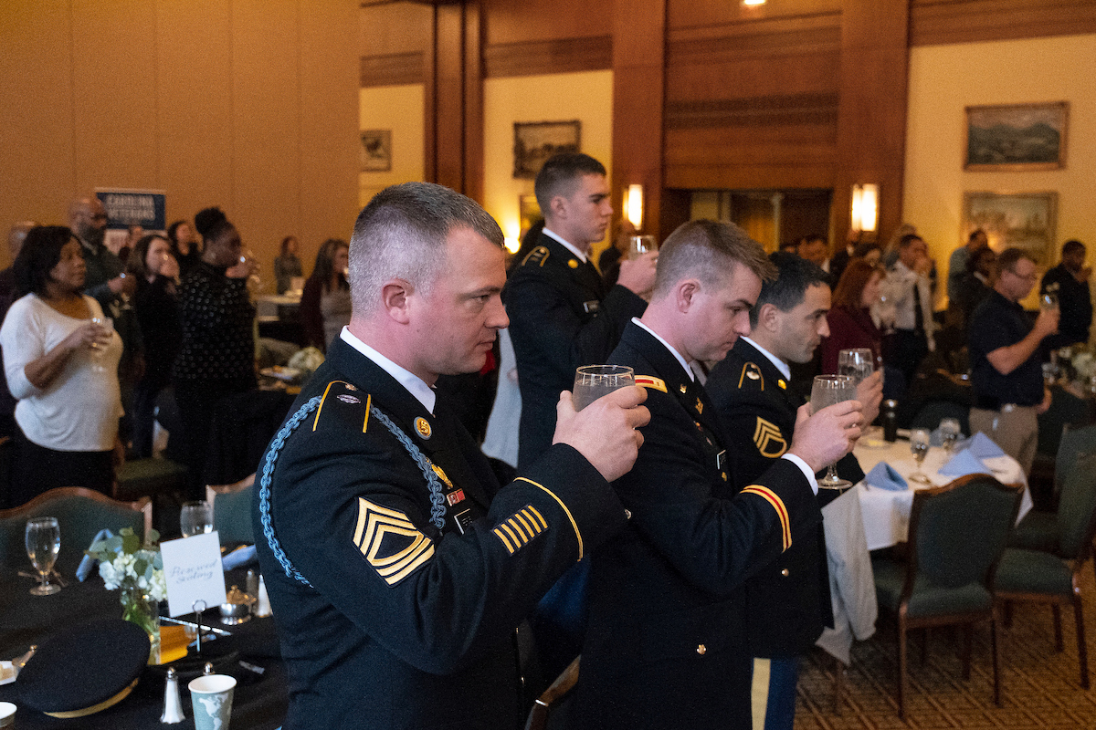 Service members hold up a glass in honor of fallen soldiers.
