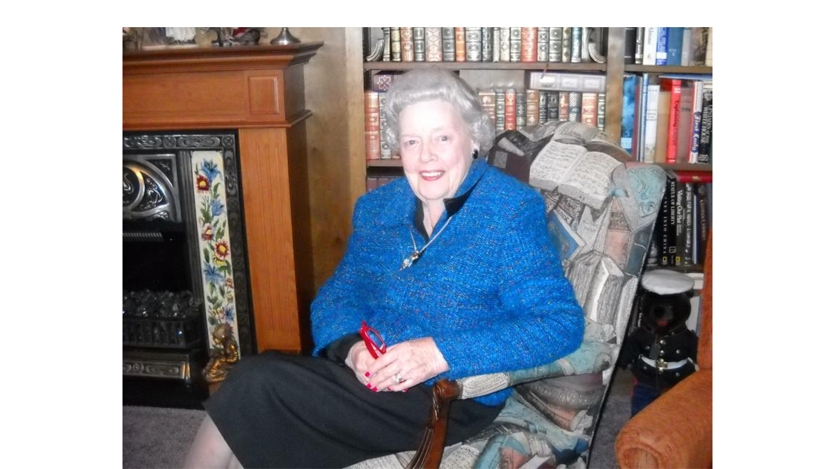 Elinor Dixon Hawkins sits in a chair.