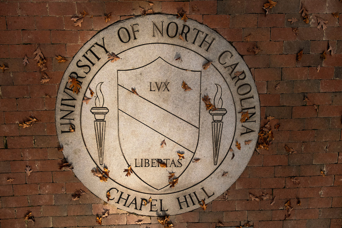 The University of North Carolina at Chapel Hill seal with fall leaves on top.