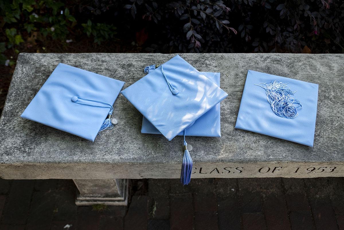 graduation caps on a bench.