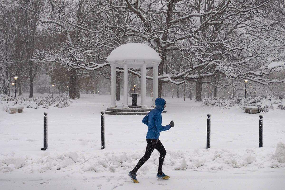 A person runs near the Old Well in the snow.