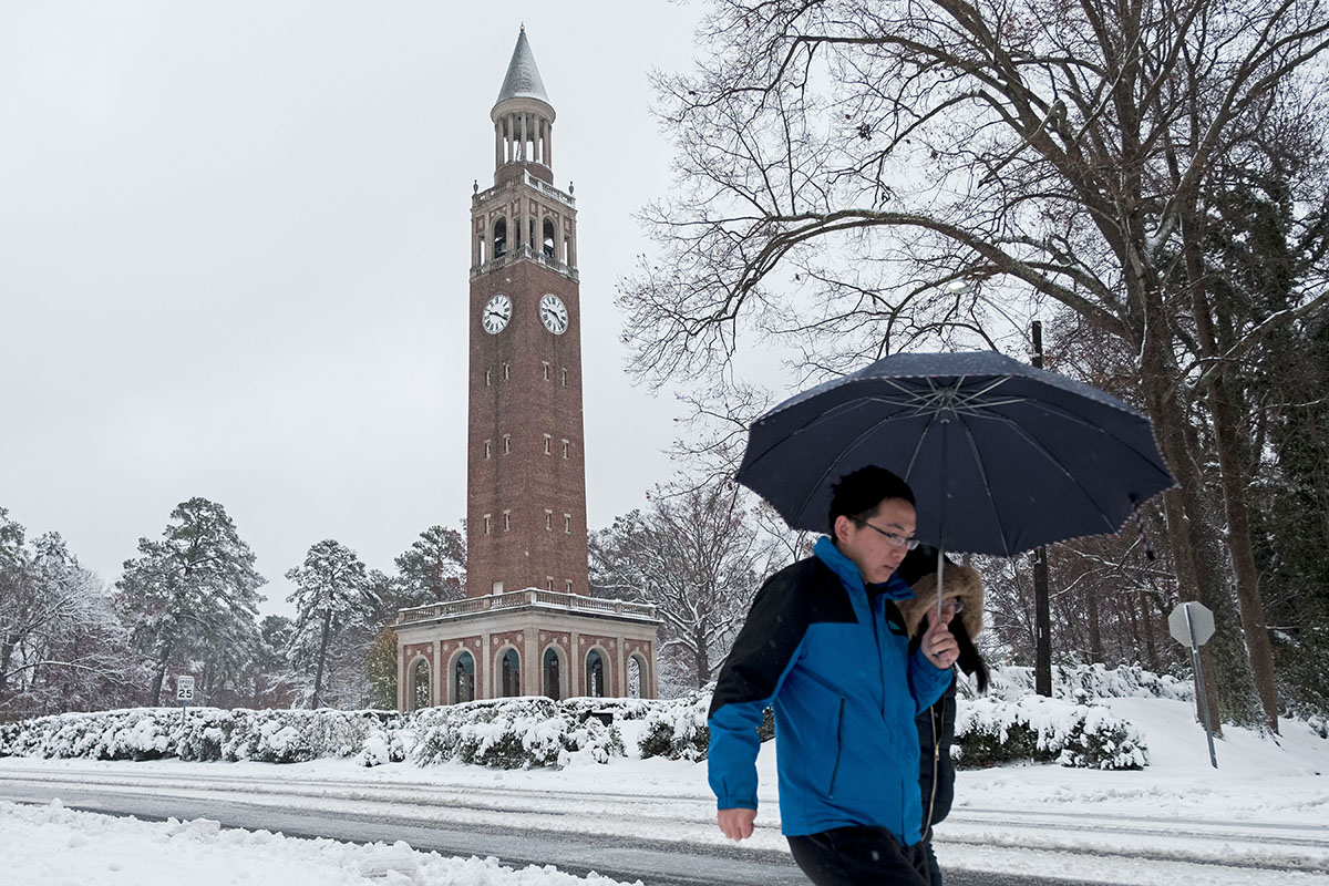 People walks in the snow near the bell tower.