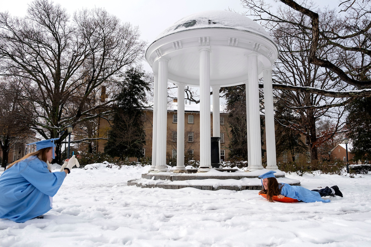 A student in a graduating gown sits on a sled.