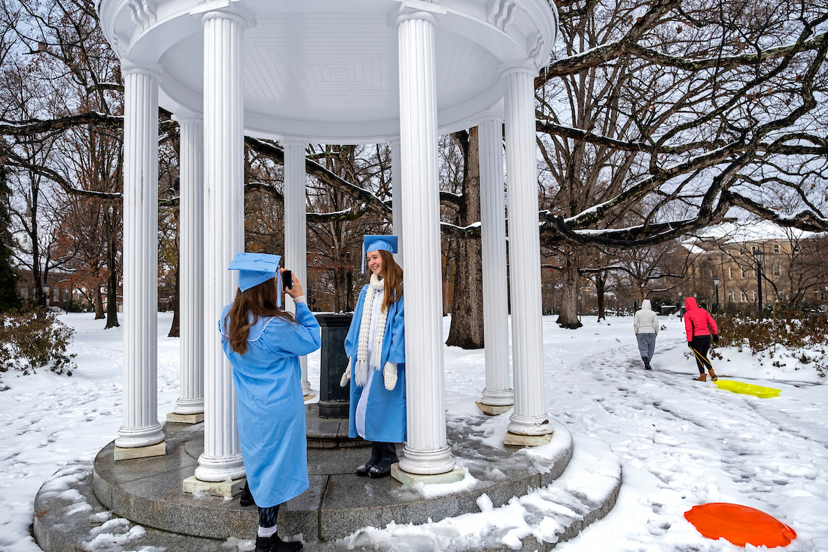 Students in graduation gowns take photos by the Old Well in the snow.