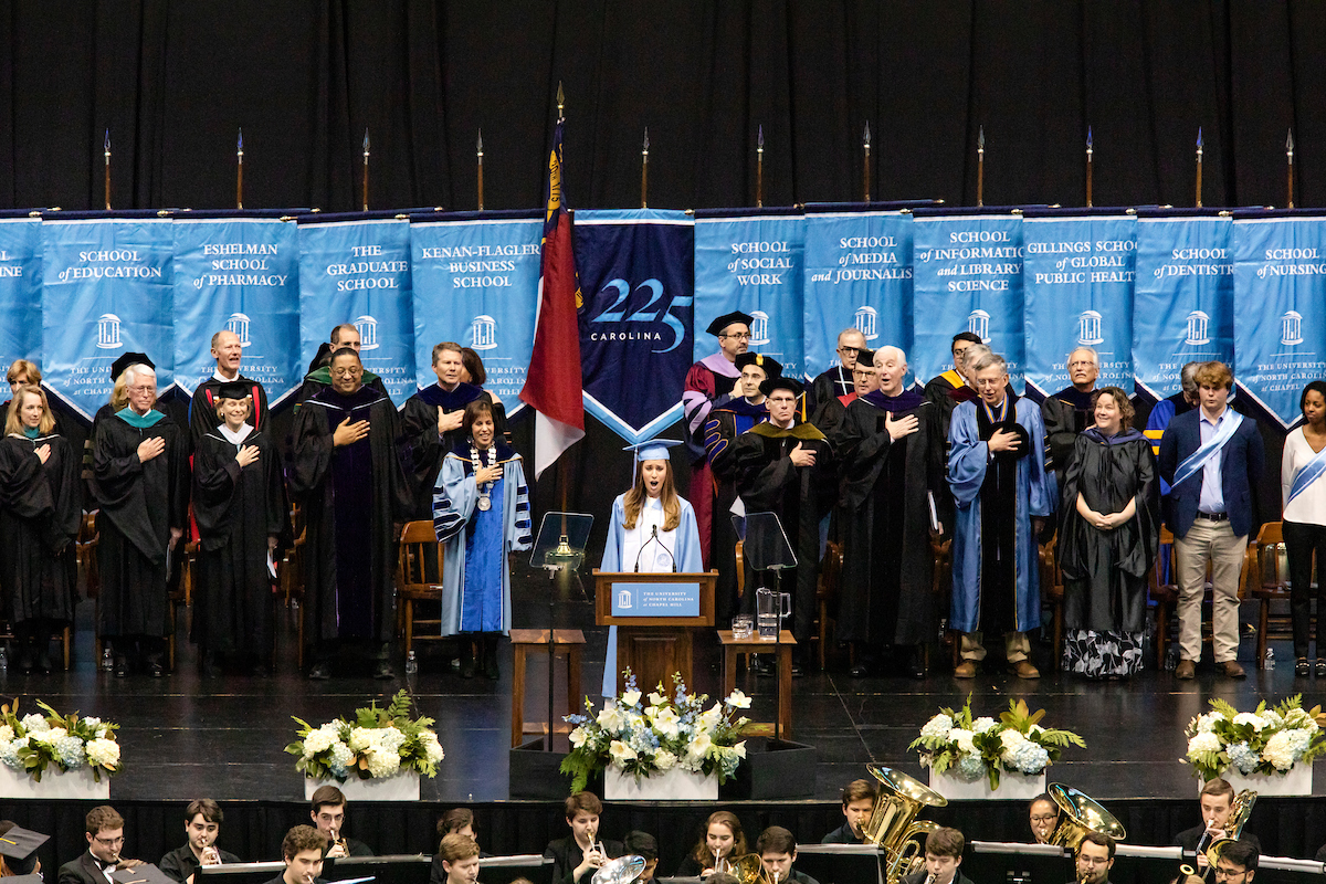 The platform party stands on the stage during commencement.