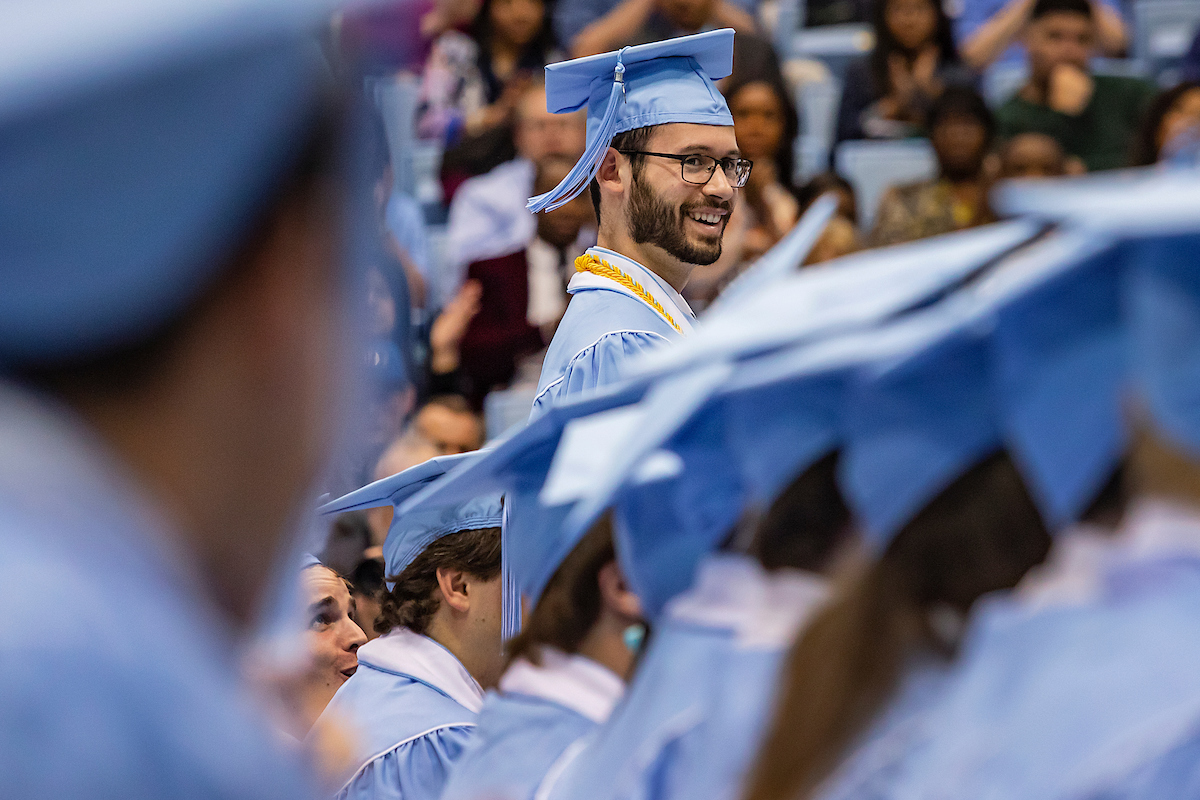 A graduate stands during commencement.