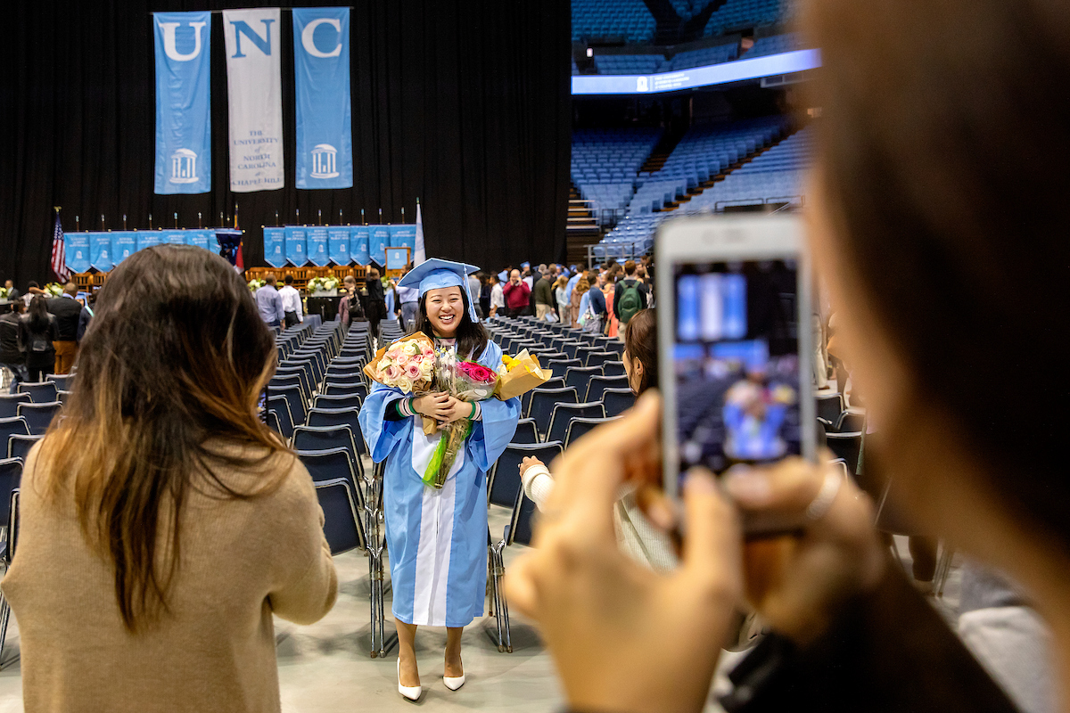 A person takes a photo of a graduate.