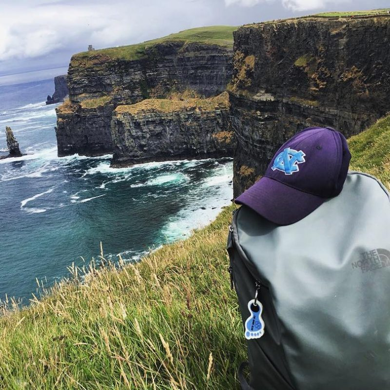 Carolina baseball cap sits on the Cliffs of Dover with the ocean in the background