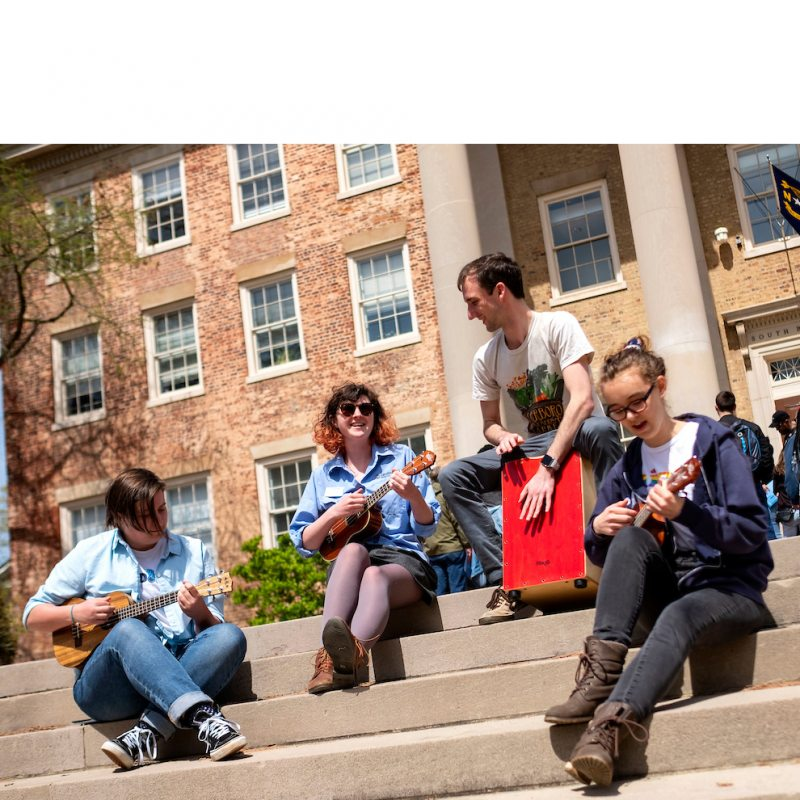 Students sit on the steps of South Building playing music.