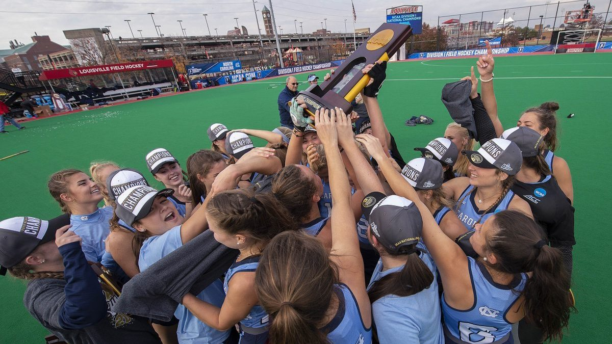 A UNC field hockey team lifts the national championship trophy.
