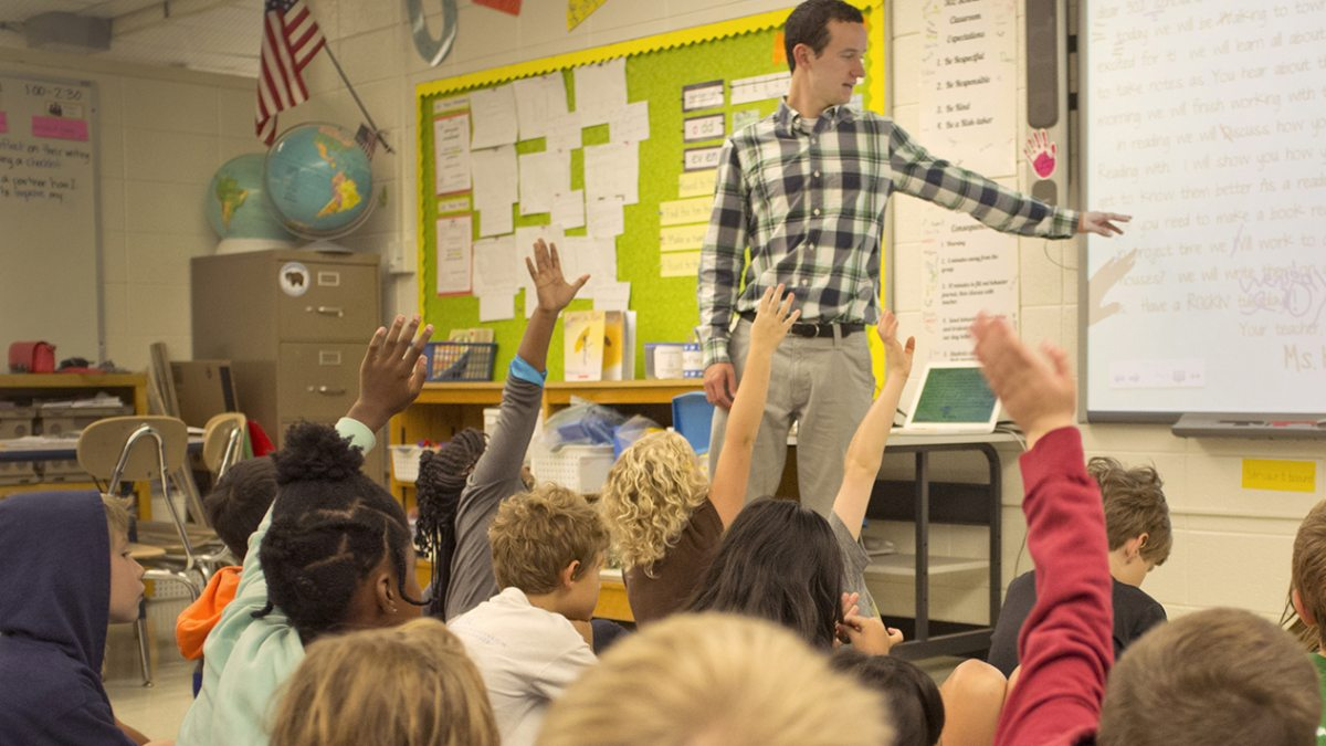A teacher points to a whiteboard as students raise their hands.