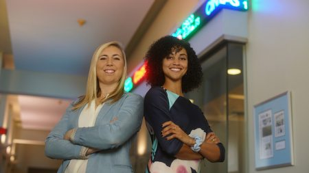 Michelle and Charlotte pose in front of the capital markets lab
