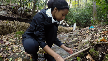 A student stands in a creek while conduct research.