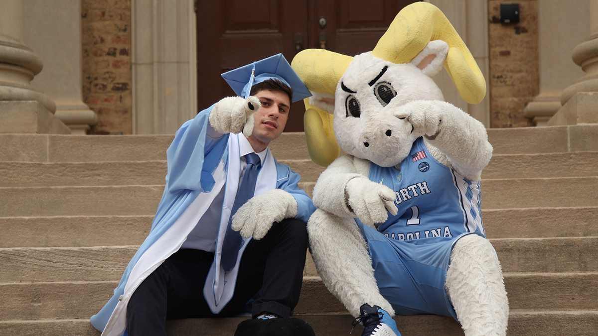 Alex Floch sits on the steps of South Building with Rameses.