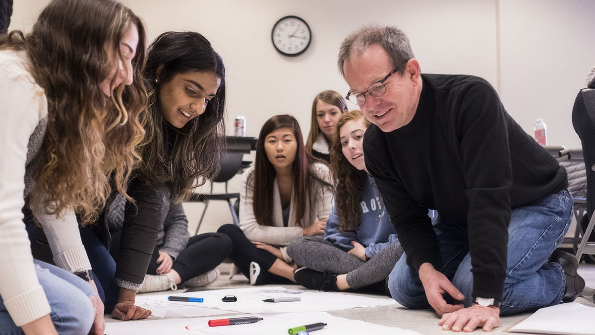 A professor sits on the floor with students who are drawing.