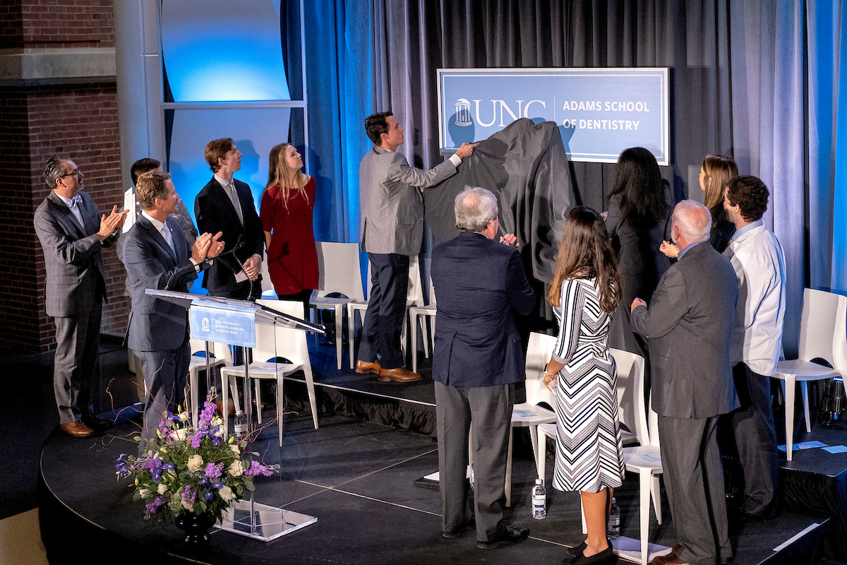People on stage unveil a new sign for the UNC Adams School of Dentistry.