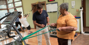 Battaligni works with woman using exercise bands