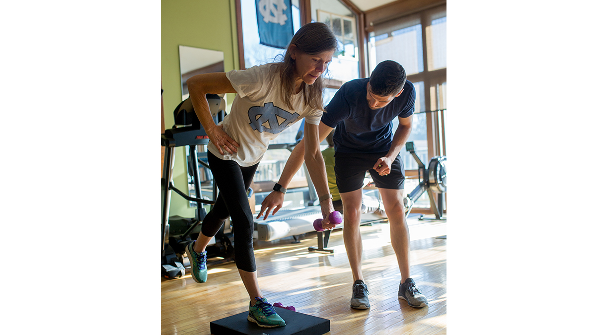Woman in Carolina t-shirt balances with weights while trainer directs her
