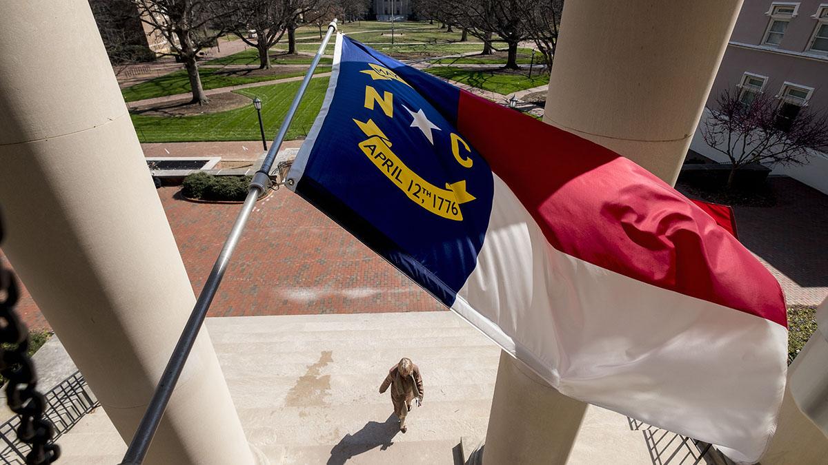 A North Carolina flag flies above South Building.