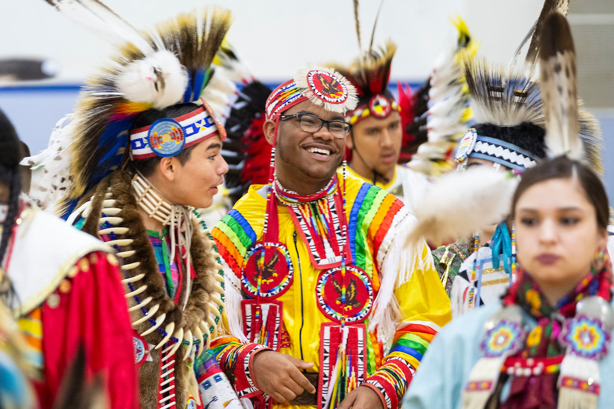 Powwow dancers laugh while standing in line.