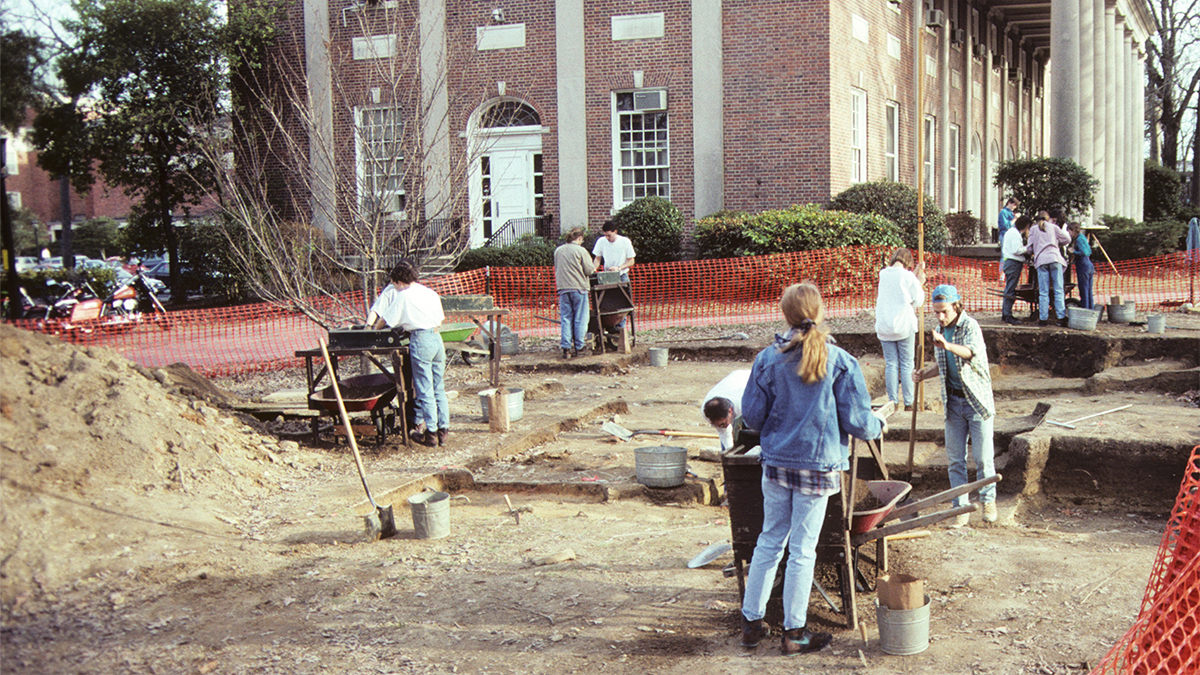 Students work at an archaeological near Graham Memorial Hall.