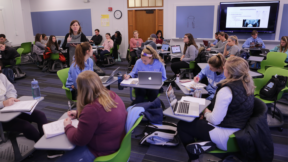 Teaching professor Meredith Petschauer lectures in a classroom with no desks.
