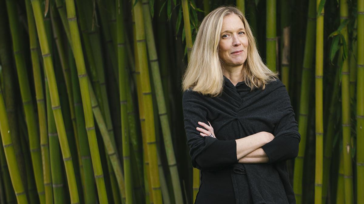 Elizabeth Stringer stands near bamboo.