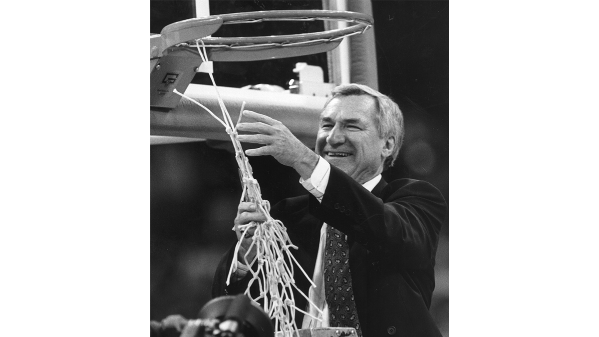 Dean Smith cuts down the net following a national championship game.
