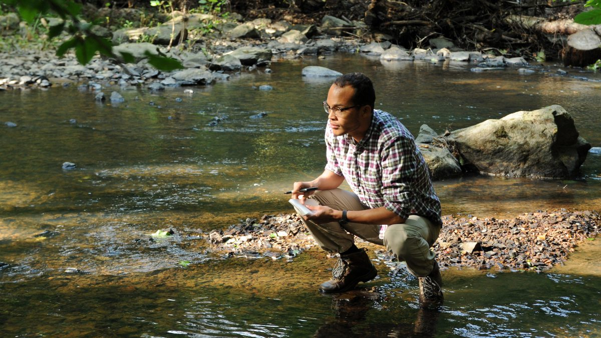 Student crouches at the edge of a river to test water quality