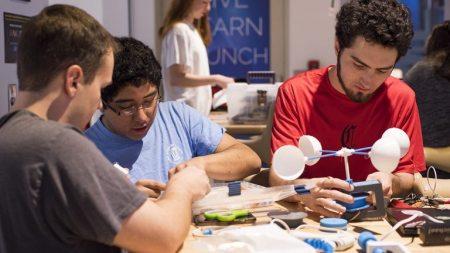 Three students work on devices at the Makeathon