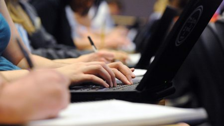 Close up of student hands on laptops and notepads