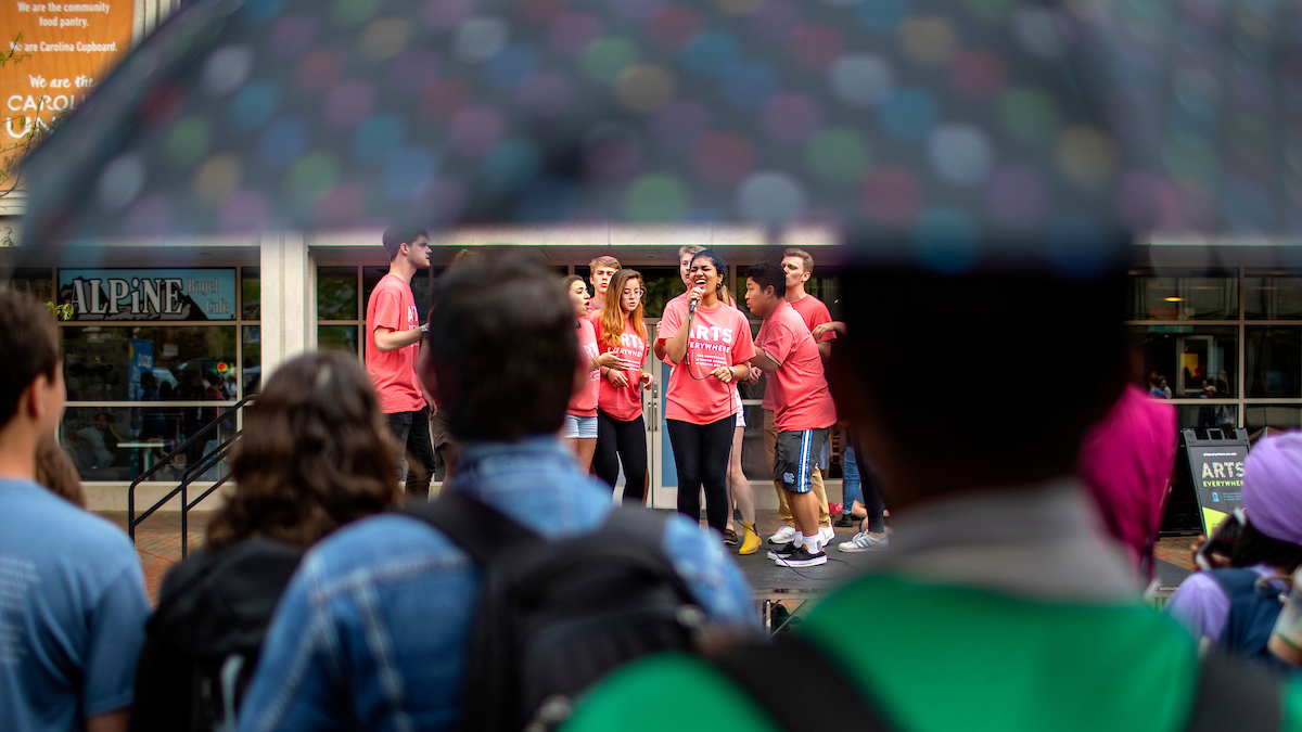 A student group sings on stage near the Pit.