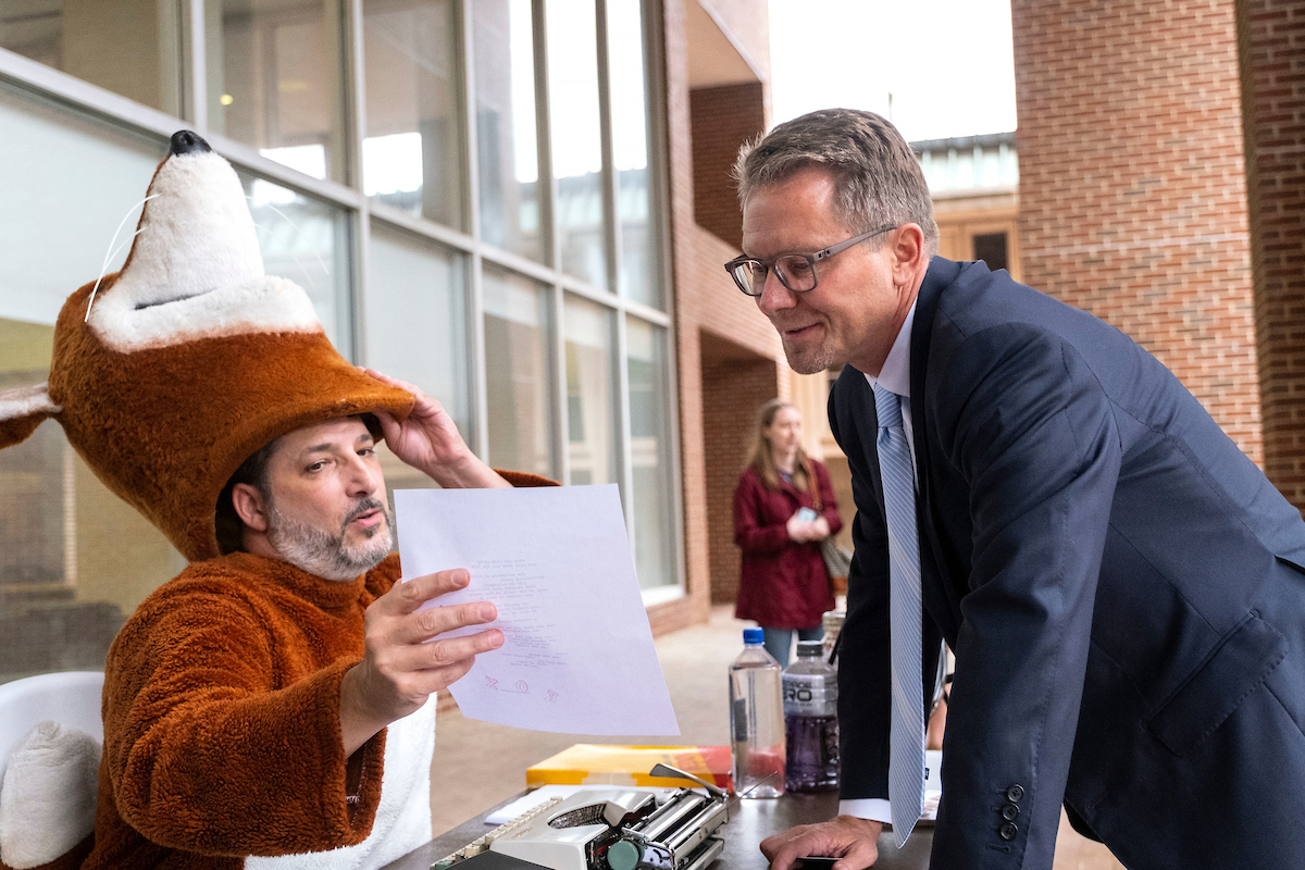 A man dressed in a fox costume holds a piece of paper.