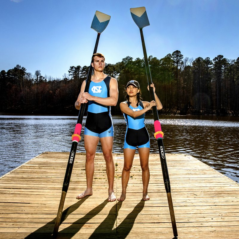 Students hold rowing oars by a lake.
