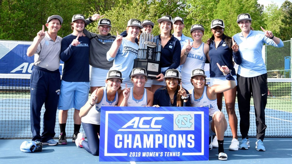 The women's tennis team holds an ACC Champions banner.