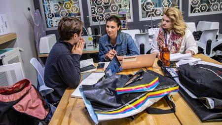 Three students talk around a laptop.